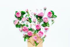 La fin vers le haut de la disposition créative avec les fleurs roses de thé rose, pétales volent hors de l'enveloppe croped de pa Photo libre de droits