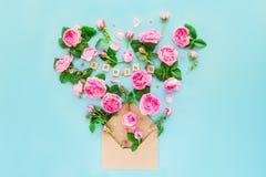 La fin vers le haut de la disposition créative avec les fleurs roses de thé rose, pétales volent hors de l'enveloppe de papier de Images stock