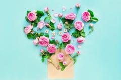 La fin vers le haut de la disposition créative avec les fleurs roses de thé rose, pétales volent hors de l'enveloppe de papier de Images libres de droits