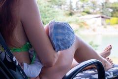 La fin vers le haut de la femme et de la nouvelle mère allaitant le moment de bébé étend l'extérieur sur la chaise de plate-forme image libre de droits