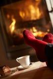 La fin vers le haut de homme des pieds détendant par le feu de bois confortable Photos libres de droits