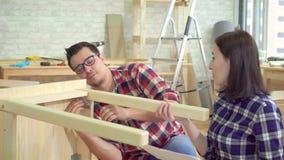 La fin vers le haut de jeunes couples mariés recueille une table de chevet dans un nouvel appartement moderne banque de vidéos