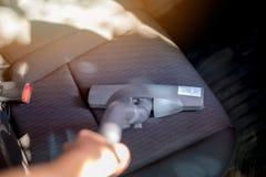 La fin vers le haut de l'aspirateur nettoient à l'aspirateur le coussin de voiture images libres de droits