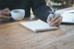 La fin vers le haut de l'homme d'affaires écrivent le carnet et et tenant la tasse de café o photos stock