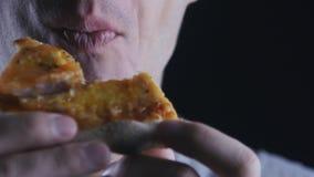 La fin vers le haut de l'homme mange un morceau de pizza délicieuse Le procédé de consommation de pizza filmé par la fin vers le  clips vidéos