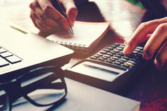La fin vers le haut de la main de femme utilisant la calculatrice et l'écriture font la note avec Photos libres de droits