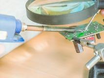 La fin vers le haut de la main de la jeune fille asiatique créent le projet de DIY par solderin images libres de droits