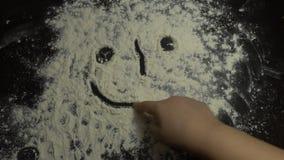 La fin vers le haut de la main du ` s d'enfant dessine sur la farine HD Photographie stock libre de droits