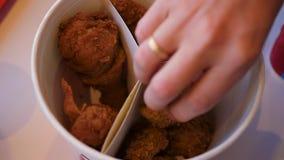 La fin vers le haut de la main prend un morceau de poulet frit sur le plat Restaurant d'aliments de préparation rapide banque de vidéos