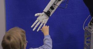 La fin vers le haut de la vue de la main de garçon tient la main en plastique mobile blanche du robot de humanoïde dans l'exposit banque de vidéos