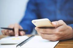 La fin vers le haut de la main d'homme d'affaires écrit dans un carnet et utilise la calculatrice photo stock