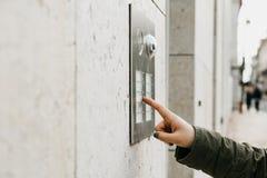 La fin vers le haut de la main femelle appuie sur le bouton de doorphone La fille appelle l'interphone Images stock