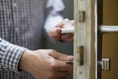 La fin vers le haut de la main de personne dans la chemise à carreaux ouvre la porte utilisant des clés photographie stock libre de droits