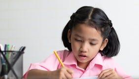 La fin vers le haut de la petite fille fait le travail attentivement images libres de droits