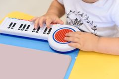 La fin vers le haut de petites mains joue sur un piano de jouet image stock