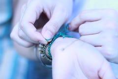 La fin vers le haut des couples de marié de main a mis donner le bracelet sur la jeune mariée images stock