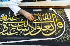 La fin vers le haut des hommes créent des vers islamiques de koran de calligraphie Photographie stock