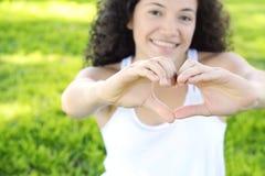 La fin vers le haut des mains de femme de foyer montrent le symbole d'amour Photographie stock