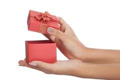 La fin vers le haut des mains ouvrent un boîte-cadeau rouge Images stock
