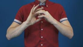 La fin vers le haut du magicien dans la chemise rouge exécutent tour de magie disparaissent en cigarette de mains banque de vidéos