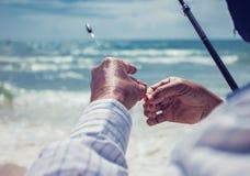 La fin vers le haut du pêcheur met le ver sur un hameçon dans la plage Image libre de droits
