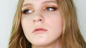 La fin vers le haut du portrait du beau visage de jeune femme avec le bronze lumineux composent regarder l'appareil-photo, puis d clips vidéos