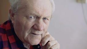 La fin vers le haut du portrait des regards de vieil homme à la fenêtre avec pense alors des sourires à l'appareil-photo banque de vidéos