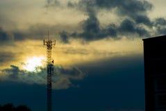La fin vers le haut du poteau de téléphone de silhouette ont la lumière du soleil d'ove dans l'aube image libre de droits