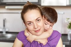 La fin vers le haut du tir du beau petit enfant embrasse passionément sa mère, aime son beaucoup, exprime ses sentiments véridiqu images stock