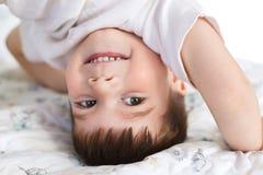La fin vers le haut du tir du petit garçon de sourire beau se tient sur la tête, étant heureuse, a l'amusement après que bon dorm photos libres de droits