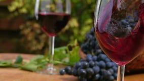 La fin vers le haut du vin rouge est versée dans un verre clips vidéos