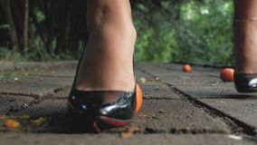 La fine della ragazza del piede su in scarpe nere del brevetto-cuoio ha schiacciato un mandarino su una tegola di cemento armato  archivi video