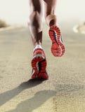 La fine di retrovisione sulle forti scarpe da corsa femminili atletiche delle gambe mette in mostra pareggiare della donna immagini stock