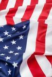 La fine di seta della bandiera americana su fondo decora Immagini Stock