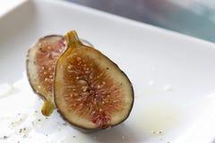 La fine di un fico ha tagliato a metà su un piatto con olio d'oliva fotografie stock