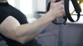 La fine di un uomo che fa un braccio spinge verso l'alto aumenta con gli anelli relativi alla ginnastica video d archivio