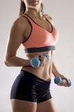 La fine potata del corpo su di giovane donna attraente nello sport copre la tenuta della testa di legno del peso Fotografia Stock
