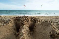 La fine su dei piedi di un uomo rintraccia sulla spiaggia sabbiosa vicino alla spiaggia Immagine Stock