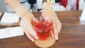 La fine su dei servire della mano ghiaccia la bevanda rosa del tè alla contro barra in caffè Fotografia Stock
