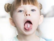 La fine su del bambino mette la pillola nella sua bocca fotografie stock libere da diritti