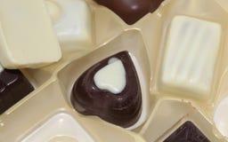 La fine su del cuore nero del cioccolato ha modellato la pralina immagini stock