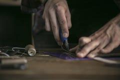 La fine su del lavoratore del cuoio della mano dell'uomo ha tagliato il pezzo di cuoio extra con il coltello Fotografia Stock
