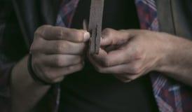 La fine su del pezzo di cuoio nel lavoratore di cuoio delle mani dell'uomo incide le strisce sottili Immagini Stock Libere da Diritti