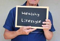 La fine su dell'uomo senior che tiene una lavagna con i buona salute di frase uguaglia la buona vita Immagini Stock