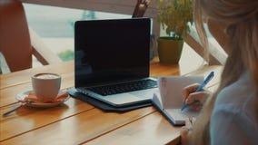 La fine su della donna di affari scrive una penna in un taccuino che esamina il computer portatile stock footage
