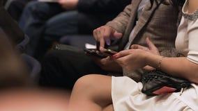 La fine su della a equipaggia e delle mani della donna azione Equipaggi e una donna che si siede ad una conferenza con i telefoni archivi video