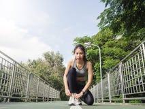 La fine su della giovane donna allaccia la sua scarpa pronta all'allenamento sull'esercitazione nel parco con il sole leggero cal Fotografia Stock