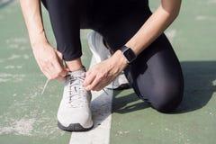 La fine su della giovane donna allaccia la sua scarpa pronta all'allenamento sull'esercitazione nel parco con il sole leggero cal Fotografia Stock Libera da Diritti