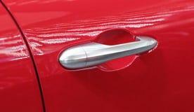 La fine su della maniglia di porta grigia dell'automobile sui precedenti rossi fotografia stock
