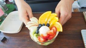 La fine su della mano serve la macedonia del gelato alla contro barra in caffè Fotografie Stock
